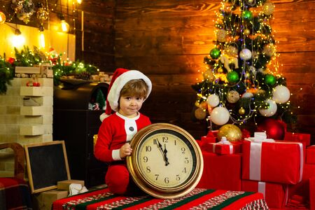 Christmas or New Year time. Cute child in santa claus hat holding red alarm clock with thumb up. Twelve Oclock midnight in retro style. Christmas decoration. clock displays just before New Year.