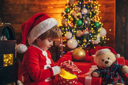 Boy child play christmas decorations. Merry and bright christmas. Childhood activity and game. Christmas attributes. Childhood memories. Family holiday. Santa boy celebrate christmas at home Фото со стока