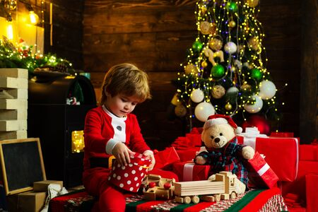 Childhood memories. Santa boy celebrate christmas at home. Boy child play near christmas tree. Merry and bright christmas. Childhood activity and game. Lovely baby enjoy christmas. Family holiday