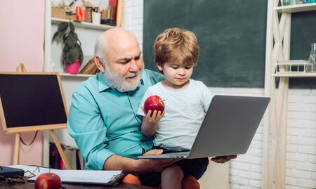 Funny little child having fun on blackboard background. Portrait of confident old male teacher. Portrait of grandfather and grandson on blackboard in classroom.