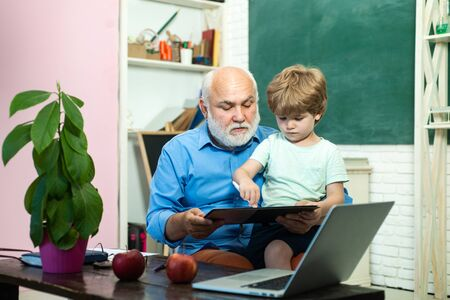 Kid with old teacher learning in class on background of blackboard. Happy cute clever boy and old tutor with book. Happy cute Grandson and Grandfather sitting at a desk indoors.