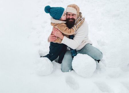 Daddy and boy smiling and hugging. Enjoying nature wintertime. Cute little child boy and happy father on snowy field outdoor. Standard-Bild - 129258288
