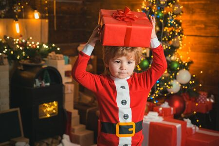 Boy cute child cheerful mood christmas gift. Family holiday. Merry and bright christmas. Lovely baby enjoy christmas. Santa boy little child celebrate christmas at home. Wish list. Childhood memories Standard-Bild - 129258300