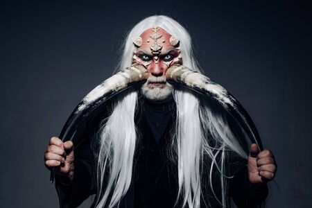 Elderly man holding two red horns. Demon head isolated on black. Ancient alchemy. Devil horns. Bearded old man dressed like Halloween monster. Druid on black background.
