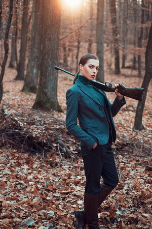 Hunter Girl with rifle in autumn forest. hunting sport. girl hunter in forest. girl with rifle. chase hunting. Gun shop. military fashion. achievements of goals. woman with weapon. 스톡 콘텐츠