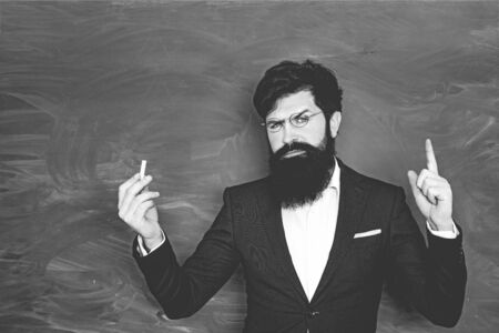 Retro bearded teacher over blackboard. Back to school and happy time. School concept. World teachers day. Professor in class on blackboard background.