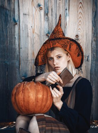 Halloween girl. Attractive witch holding pumpkin and knife for a trick or treat. Woman dressing in Halloween costume with orange witchs hat for a themed party. October festival. Wood background. Фото со стока - 129321667