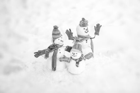 Cute snowmen family in winter Christmas landscape. Happy winter snowman family. Mother snow-woman, father snow-man and kid wishes merry Christmas and Happy New Year. Zdjęcie Seryjne - 129322256