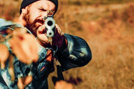 Jäger Mann. Ein Jäger mit einem Jagdgewehr und einer Jagdform, um im Wald zu jagen. Kaliber von Jagdgewehren. Jäger mit Schrotflinte auf der Jagd. Jagd ist das Töten oder Fangen von Tieren.