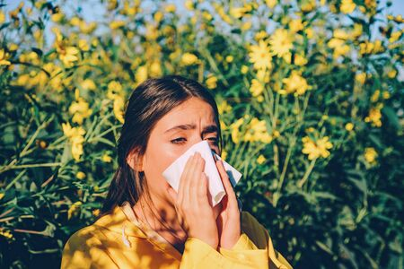 Woman got nose allergy, flu sneezing nose. The girl suffers from pollen allergy during flowering and uses napkins. Allergy.