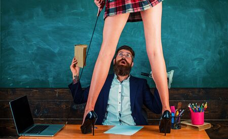Lets Talk Sex. Bearded sexology teacher looks at two sexy female students. Erotic education and sex Symbols on chalkboard. Imagens