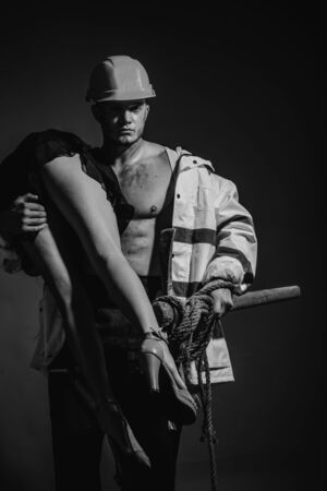 Firefighter sexy body muscle man holding saved sexy woman. Rescuer firefighter or miners - risky occupations concept. Working profession, special clothes, overalls. Hot and sexy.