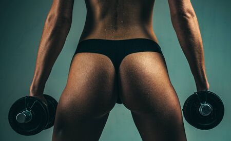 Female fitness buttocks. Butt and dumbbells. Woman working hard in the gym. Woman fitness concept.