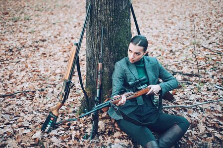 Girl with rifle in autumn forest. chase hunting. Gun shop. woman with weapon. Target shot. successful hunt. hunting sport. female hunter in forest. military fashion. 스톡 콘텐츠