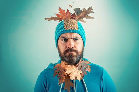 Funny autumn man. Fashion man. Surprise hipster man playing with leaves and looking at camera. Black friday shopping. Funny Man on gray leaf background. Stock Photo