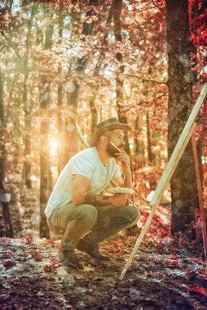Romantic and Dream. Man artist painting autumn picture. Autumn outdoor portrait of artist. He painting autumn picture. Stock Photo