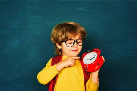 Funny pipil. Back to school. Alarm clock anxiety. Late. Kid boy holding clock alarm. Stock fotó