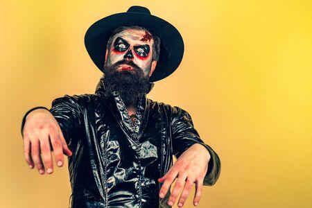 Halloween. Evil vampire man. Bearded man dressed like Halloween monster. Halloween man with pumpkin. Devil man with bloody face.