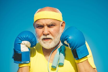 Funny bearded man standing in boxing pose. Elderly man hitting punching bag. Boxing. I love boxing. Portrait of a determined senior boxer over blue sky background.