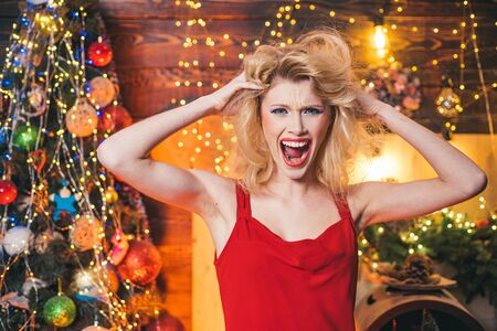 Merry Christmas and happy new year. Crazy woman. Nervous, thrilled and scared emotions. Crazy comical face. Comic grimace. Фото со стока