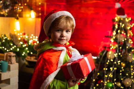 Kid enjoy winter holiday at home. Home filled with joy and love. Merry christmas and happy new year. Best wishes. Family holiday. Christmas gift. Cute little child boy play near christmas tree