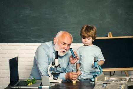 Biologie - La classe des sciences. Cours de biologie scolaire. Professeur drôle dans la salle de classe. La science. Élève souriant heureux dessinant au bureau.
