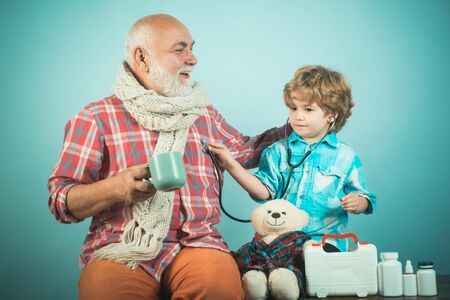 Handsome old man grandfather is having pain and his grandson supports him. Happy child pharmacist showing drug to senior man. Stock fotó
