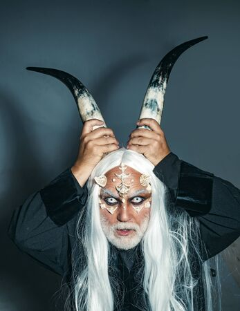 Dracula - Halloween concept. Evil vampire man. Ancient alchemy. Elderly man holding two red horns. Mysterious warrior enchanted to have thorns on his face. Horror and fantasy concept. Reklamní fotografie