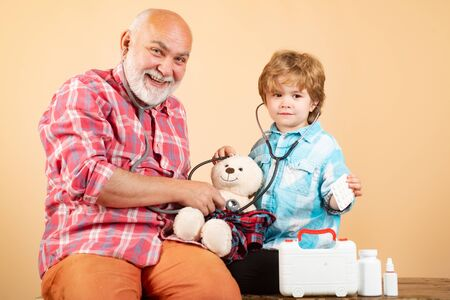 Parenting. Old man with scarf holding a blister of pills in his hands. Patient recovery is going well. Little doctor giving grandfather medicament.