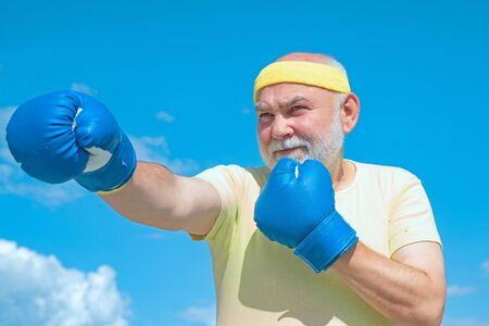 Senior sportive man in boxing stance doing exercises with boxing gloves. Active leisure. Best cardio workout.