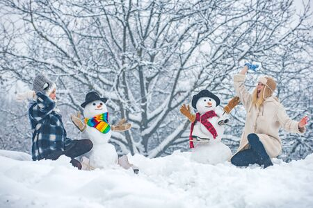 People in snow. Happy smiling girls make snowman on sunny winter day. Two smiling friends make Snowman on Christmas background. Standard-Bild - 129322228