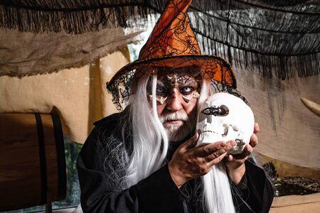 Demon with skull on Halloween party. Vampire Halloween Concept. Horror. Halloween man with Blood make up. Happy Halloween - handsome Demon isolated on dark background.