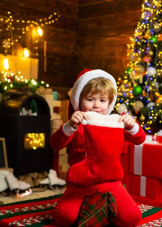 Kid boy santa hold christmas gift red sock. Christmas stocking concept. Child cheerful face got gift in christmas sock. Check contents of christmas stocking. Joy and happiness. Childhood moments