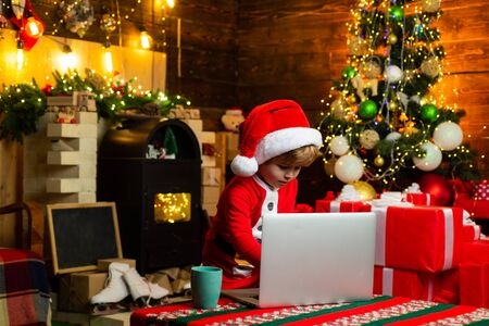 Little boy santa hat and costume having fun. Boy child with laptop near christmas tree. Buy christmas gifts online. Christmas shopping concept. Gifts service. Little genius. Santa little helper