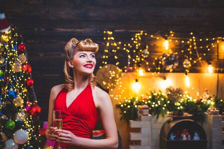 Young girl with retro hairstyle and pinup makeup over Christmas tree. Christmas Party drinks and holidays people concept. New year fashion clothes.