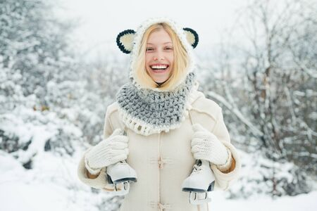 Funny winter girl is going skate outdoors. Beautiful young woman laughing outdoors. Beautiful winter woman laughing outdoors. Girl playing with snow in park.