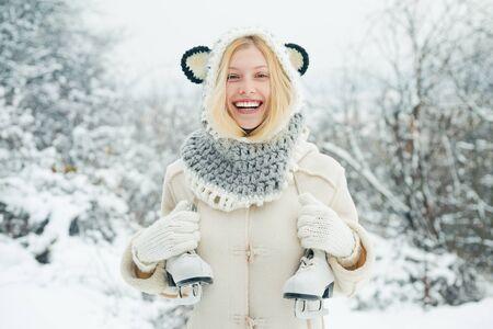 Lustiges Wintermädchen geht draußen skaten. Schöne junge Frau, die draußen lacht. Schöne Winterfrau, die draußen lacht. Mädchen, das mit Schnee im Park spielt.