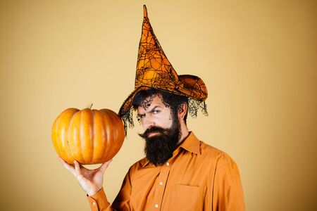Halloween man with pumpkin - Holidays celebration concept. Happy Halloween - handsome man isolated. Happy Halloween. Smiling happy man with pumpkin. Archivio Fotografico - 129640527