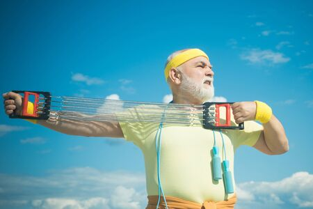 Healthcare cheerful lifestyle. Freedom retirement concept. Elderly man practicing sports on blue sky background. Grandfather sportsman. 版權商用圖片