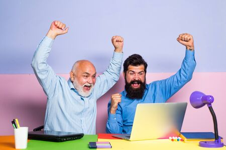 Cheerful business men team of two people group talk laughing at funny joke work together on laptop. Face expression.