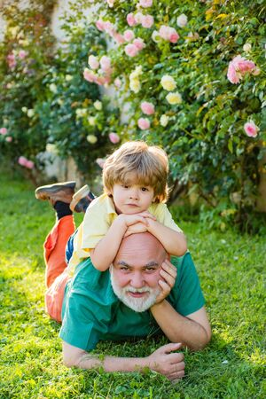 Two different generations ages: grandfather and grandson together. Happy loving family. Happy grandfather and child grandson laugh and have fun together in summer in nature. Standard-Bild - 129640524