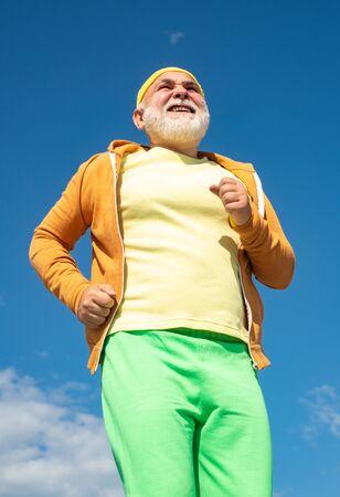 Senior man running in sunny nature. Senior male is enjoying sporty lifestyle. Senior man exercising on blue sky. Cheerful senior jogging in sportswear on sky background.
