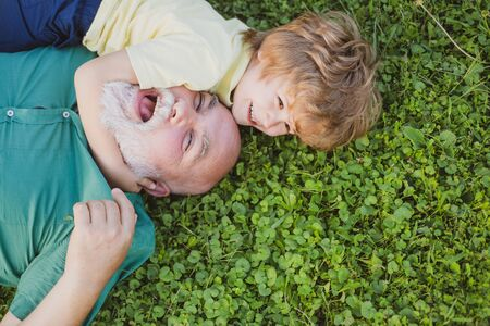 Happy child with Grandfather embracing and hugging on green grass. Grandson embrace his grandfather. Happy grandfather and grandson relaxing together.