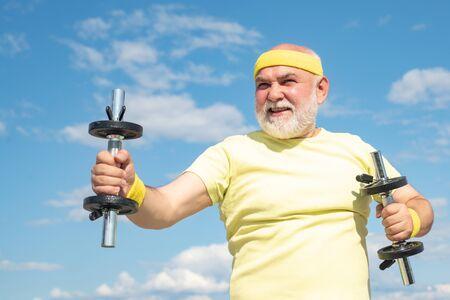 Senior sportman lifting dumbbells. Healthy lifestyle concept. Like sports. Elderly man workout. Reklamní fotografie