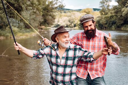 Fishing in river. Portrait of cheerful two bearded men fishing. Difference between fly fishing and regular fishing. Man fisherman catches a fish.