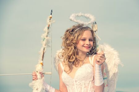 Valentines day card. A beautiful teen with blonde curly hair and a bow and arrow as cupid - Valentines Day. Little girl with angel wings and halo
