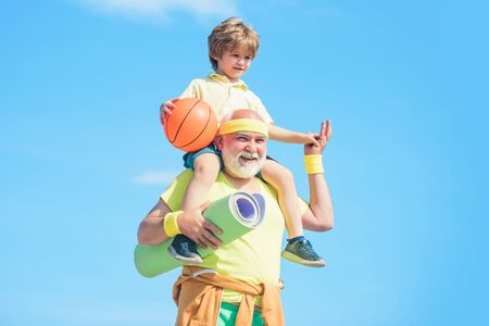 Portrait of a healthy father and son working out over blue sky background. Active healthy life for family. Fitness and active lifestyle concept - copy space. 写真素材