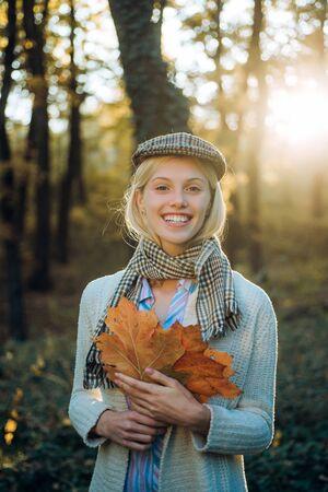 Niña divertida sonriente jugando con hojas y mirando a cámara. Otoño de mujer. Mujer de otoño divirtiéndose en el parque y sonriendo. Mujer sorpresa jugando con hojas y mirando a cámara.