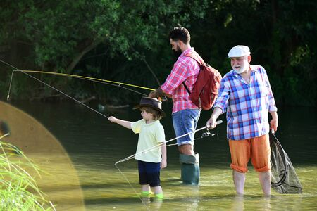 Man teaching kids how to fish in river. Little boy fly fishing on a lake with his father and grandfather. Reklamní fotografie