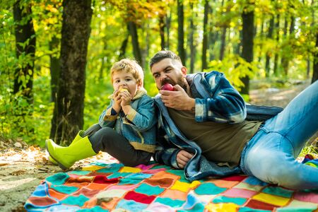 Man with beard, dad with young son in autumn park. Dad and son in sweaters in the park. Happy joyful father with a cute son in cowboy hat, family, travel, vacation, fathers day - concept. Archivio Fotografico - 129640606